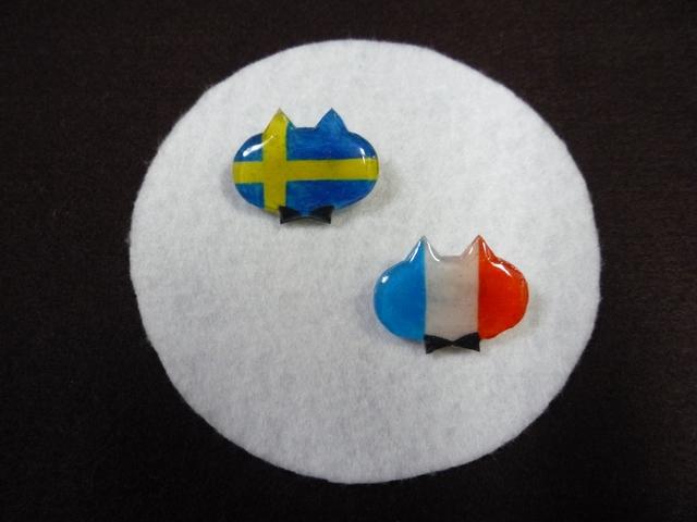 ねこモチーフの国旗ブローチ