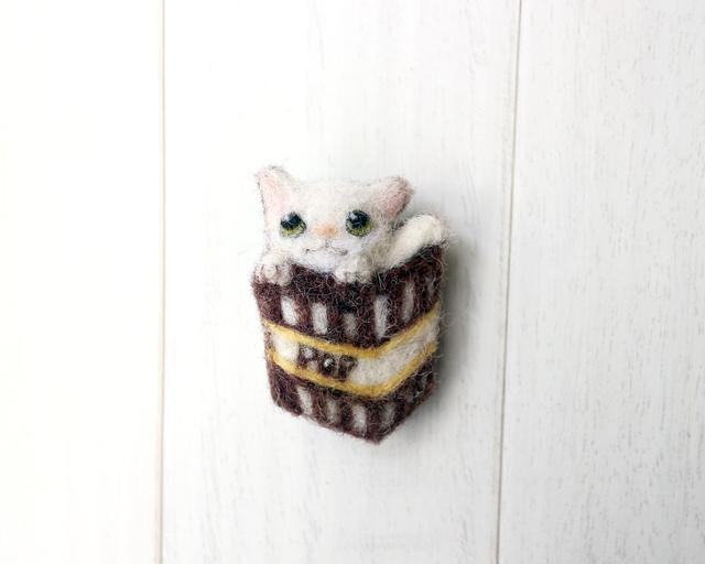 ポップコーンバケットに入った白猫のブ...
