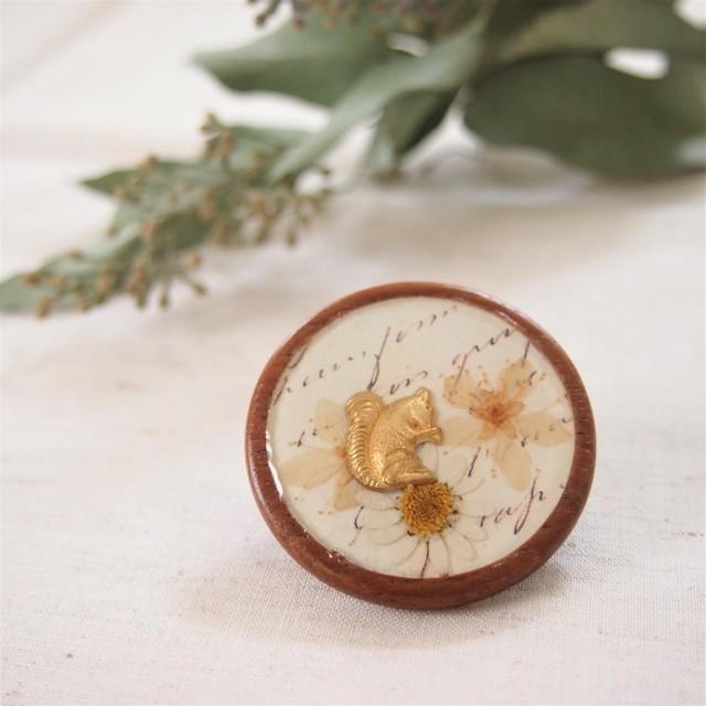 お花畑で頬張るりすの木製ブローチ