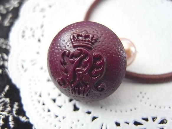封蝋の様なワイン色のエムブレムボタンのヘアゴム
