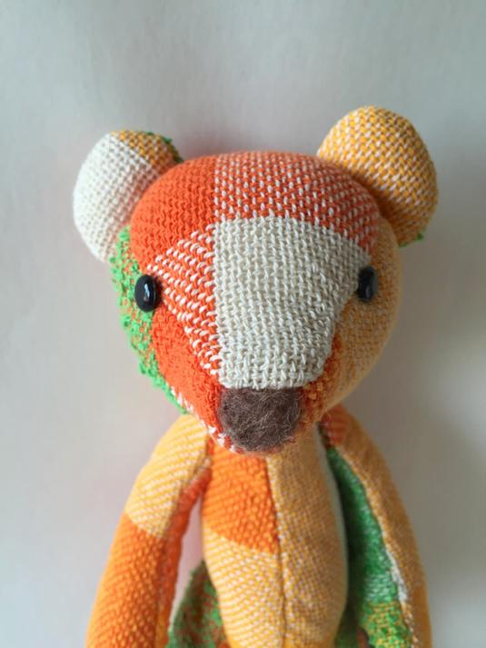 手織り布のテディベア (橙緑)