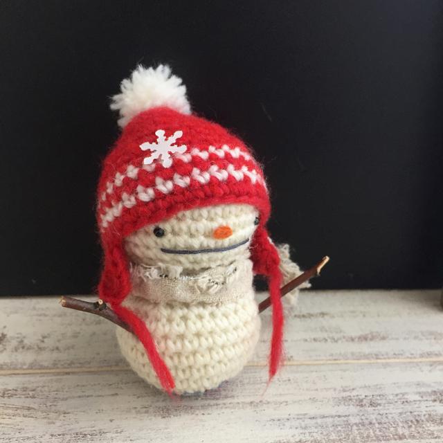 小枝の手の雪だるま 赤い帽子